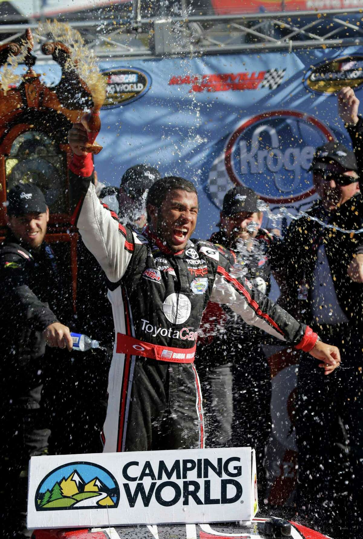 Driver Darrell Wallace Jr. celebrates in Victory Lane winning the NASCAR Truck Series auto race at Martinsville Speedway in Martinsville, Va., Saturday, Oct. 26, 2013. (AP Photo/Steve Helber) ORG XMIT: VASH108