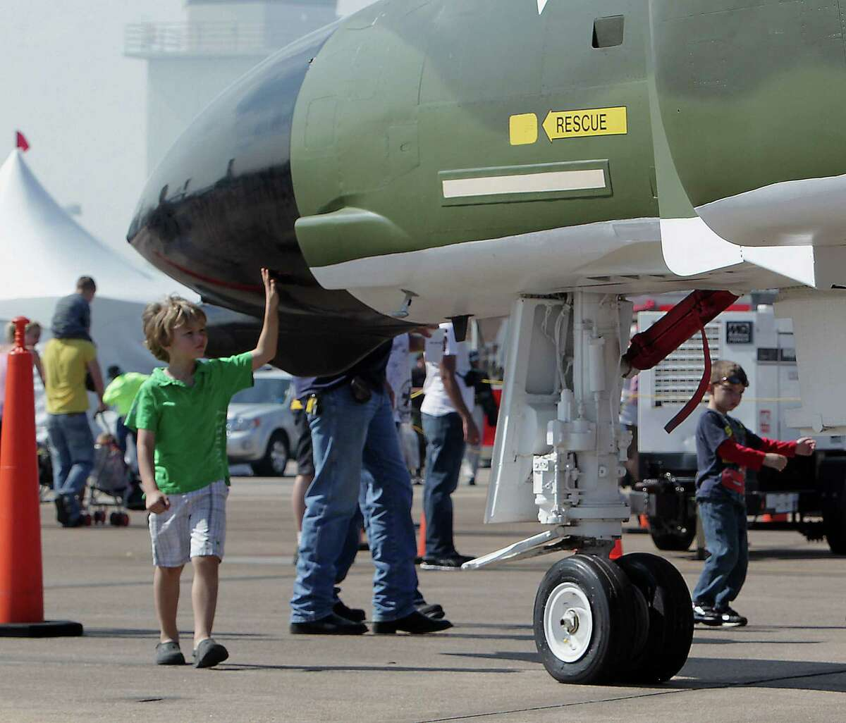 Five-year-old Wyatt Fieber runs his hands along a jet airplane on display at the Wings Over Houston Airshow at Ellington Airport Saturday, Oct. 26, 2013, in Houston.