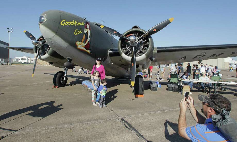 Beau Brown, right, takes a photograph of his daughter Makayla Brown, left, his mother Delores Brown, center 2nd from left, and his son Gavin Brown, 2nd from right, in front of a Lockheed C-60 airplane during the Wings Over Houston Airshow at Ellington Airport Saturday, Oct. 26, 2013, in Houston. Photo: James Nielsen, Houston Chronicle / © 2013  Houston Chronicle