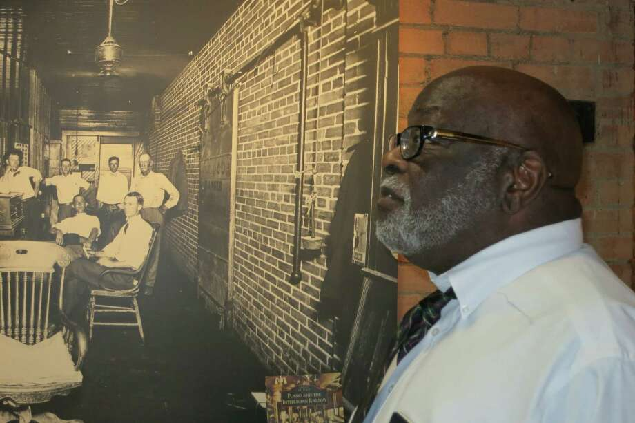 Roberty Haynes, curator of the Interurban Museum, with a photograph of the office crew at Plano's interurban depot in the 1930s, in Plano. Photo: Joe Holley, Houston Chronicle / Houston Chronicle