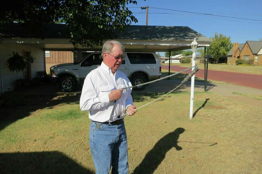 Jerry Pate Long demonstrates his dowsing technique, in Paducah.  Drive through Paducah, in northwest Texas, and what you see is a dying town. The 1930s-era Cottle County Courthouse is hemmed in on all sides by abandoned brick buildings, several of them collapsed in on themselves. It wasn't that long ago that the once-sturdy structures housed thriving cafes, drug stores, a couple of department stores, a variety store, hardware stores, a large hotel. Photo: Joe Holley, Houston Chronicle / Houston Chronicle