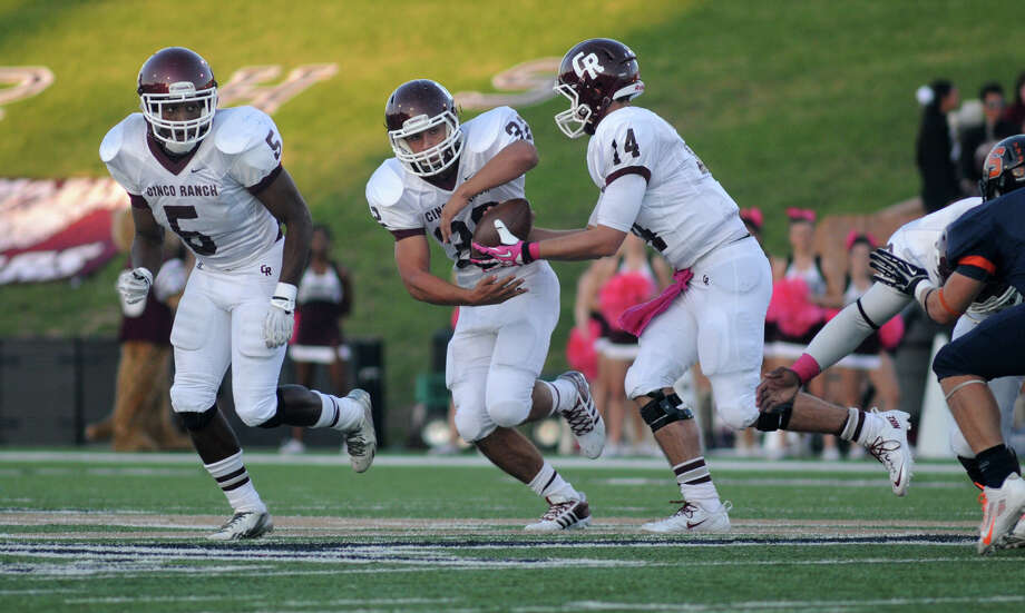 Cinco Ranch senior running back Blake Hirsch, center, takes a handoff from senior quarterback Luke Klingler (#14) behind senior teammate Denzell Bates (#5) during first quarter action of their district matchup at Rhodes Stadium in Katy on Saturday. Photo: Jerry Baker, For The Chronicle