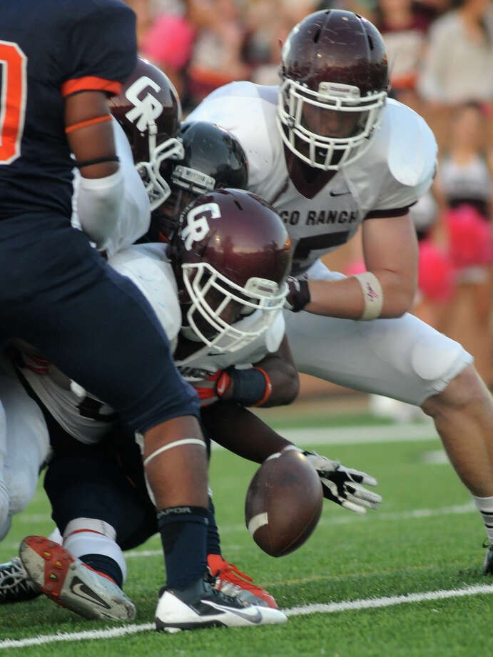 Cinco Ranch senior running back Denzell Bates, center, drops the ball after crossing the goal line on his first quarter touchdown against Seven Lakes at Rhodes Stadium in Katy on Saturday. Photo: Jerry Baker, For The Chronicle