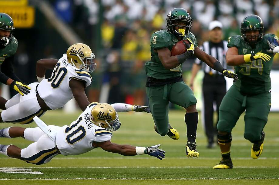 UCLA's Myles Jacks (30) and Fabian Moreau (10) can't stop Oregon's Byron Marshall from scoring one of his three touchdowns. Photo: Jonathan Ferrey, Getty Images