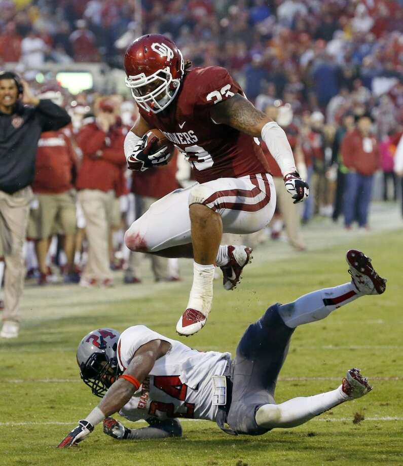 Oklahoma fullback Trey Millard (33) jumps over Texas Tech defensive back Bruce Jones (24) in the fourth quarter of an NCAA college football game in Norman, Okla., Saturday, Oct. 26, 2013. Oklahoma won 38-30. Photo: Sue Ogrocki, Associated Press