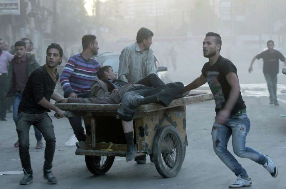 Two injured men are transported following shelling between pro-government forces and rebels in the major city of Aleppo. Photo: Karam Al-Masri / Getty Images