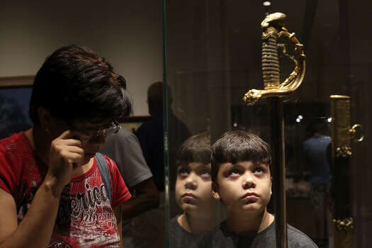 Teresa Lesczynski and her son, Ian Lesczynski, 9, view Santa Anna's sword Saturday at the Briscoe Western Art Museum, where visitors can see the long and varied history of Texas' settlement.