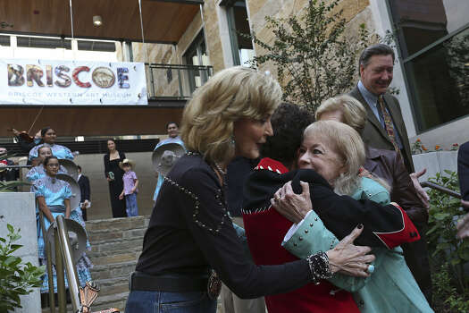 Tracy Wolff (from left) embraces Debbie Montford and Janey Briscoe Marmion, the daughter of Dolph Briscoe, Saturday during the grand opening celebration for the Briscoe Western Art Museum in San Antonio.