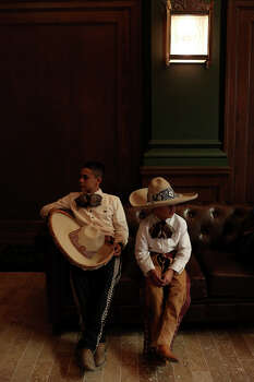 Edmundo Rios III, 17, and Diego Rivera, 8, rest inside the Briscoe Western Art Museum after performing with the San Antonio Charro Association during the grand opening celebration for the museum in San Antonio on Saturday, Oct. 26, 2013. Photo: San Antonio Express-News / San Antonio Express-News