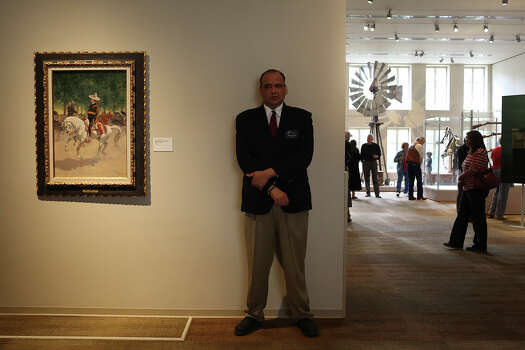 "Safety officer Julian Sanchez guards ""A Dandy on the Paseo de la Reforma, Mexico City, 1890,"" a painting by Frederic Remington, during the grand opening celebration for the Briscoe Western Art Museum in San Antonio on Saturday, Oct. 26, 2013. Patrons must view the painting from behind the white lines on the ground in front of the painting. Photo: San Antonio Express-News / San Antonio Express-News"