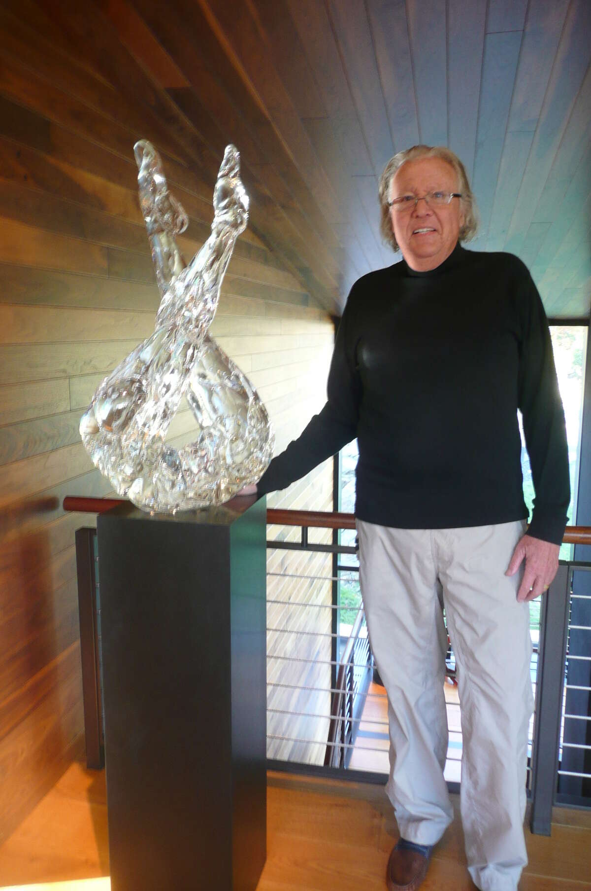 Seven Bridges Foundation founder and art collector Richard McKenzie stands next to the glass sculpture, Sentinel by Martin Blank.