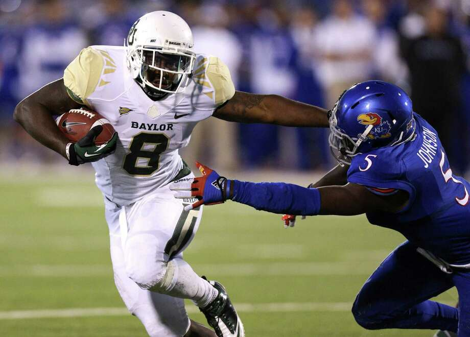 Baylor's Glasco Martin runs past Kansas' Isaiah Johnson for a TD in the first quarter. The Bears earned their school-record 11th straight win. Photo: Ed Zurga / Associated Press