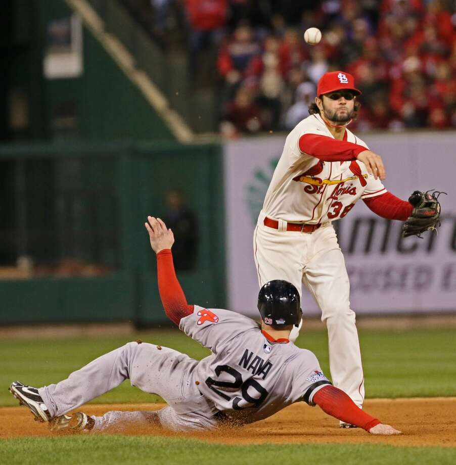 Cardinals shortstop Pete Kozma turns a double play, forcing out Daniel Nava of the Red Sox at second base. Photo: Chris Lee, McClatchy-Tribune News Service