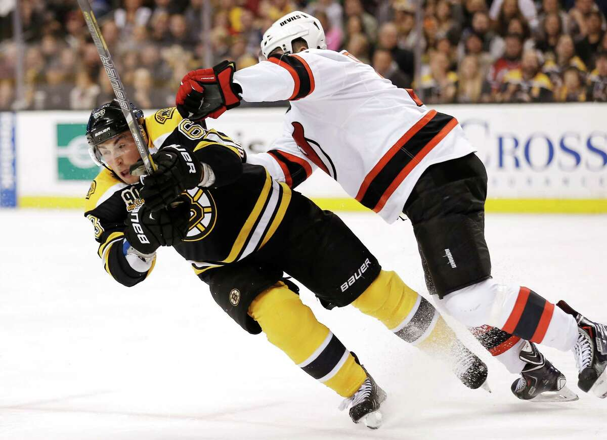 Boston Bruins' Brad Marchand, left, is checked by New Jersey Devils' Marek Zidlicky, of the Czech Republic, during the second period of an NHL hockey game in Boston, Saturday, Oct. 26, 2013. (AP Photo/Winslow Townson) ORG XMIT: BXG107