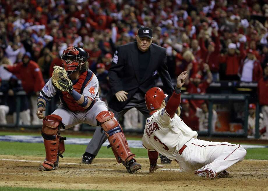 The Cardinals' Carlos Beltran slides safely past Red Sox catcher Jarrod Saltalamacchia during the seventh inning of Game 3 on Saturday in St. Louis. Beltran scored from second on a double from Matt Holliday. Photo: Matt Slocum / Associated Press