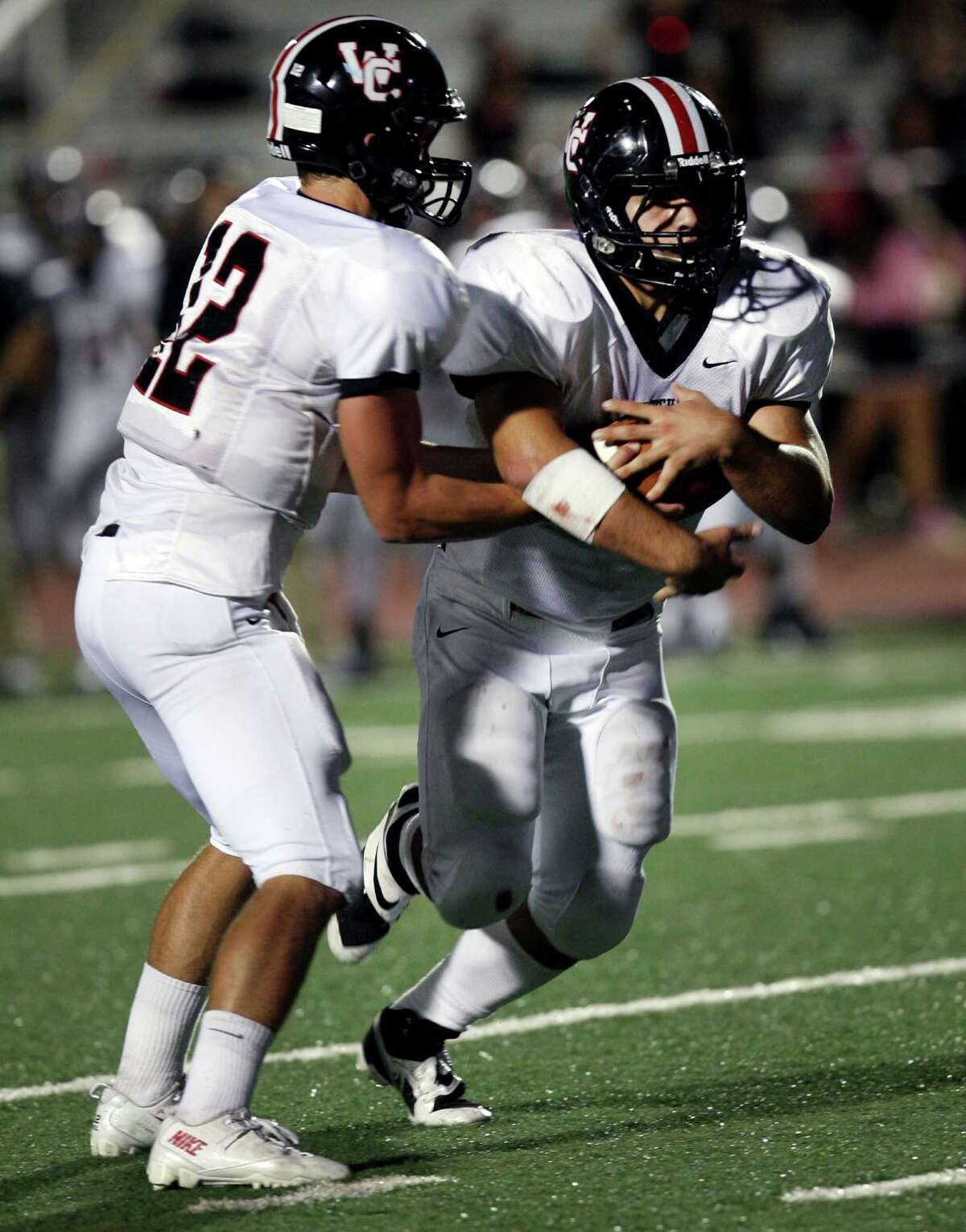 Churchill High School's Nate Peason passes off the ball to Nicholas Smisek during the first half of the game against Roosevelt Saturday, Oct. 26, 2013 at Comalander Stadium.
