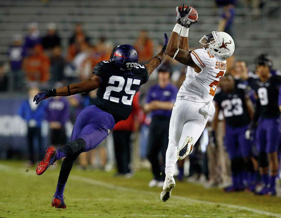 FORT WORTH, TX - OCTOBER 26:  Kendall Sanders #2 of the Texas Longhorns pulls in a pass against Kevin White #25 of the TCU Horned Frogs in the third quarter at Amon G. Carter Stadium on October 26, 2013 in Fort Worth, Texas. Photo: Tom Pennington, Getty Images / 2013 Getty Images