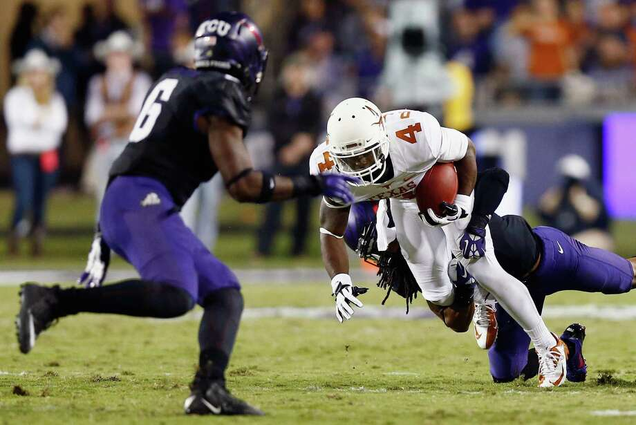 FORT WORTH, TX - OCTOBER 26:  Daje Johnson #4 of the Texas Longhorns carries the ball against Elisha Olabode #6 of the TCU Horned Frogs and Jason Verrett #2 of the TCU Horned Frogs in the second quarter at Amon G. Carter Stadium on October 26, 2013 in Fort Worth, Texas. Photo: Tom Pennington, Getty Images / 2013 Getty Images