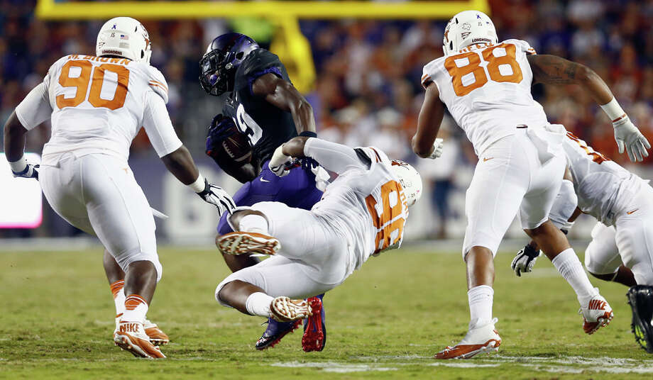 FORT WORTH, TX - OCTOBER 26:  Jordan Moore #29 of the TCU Horned Frogs carries the ball against Chris Whaley #96 of the Texas Longhorns, Malcom Brown #90 of the Texas Longhorns, and Cedric Reed #88 of the Texas Longhorns in the first quarter at Amon G. Carter Stadium on October 26, 2013 in Fort Worth, Texas. Photo: Tom Pennington, Getty Images / 2013 Getty Images