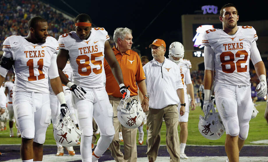 FORT WORTH, TX - OCTOBER 26:  Head coach Mack Brown of the Texas Longhorns walks off the field with his team after play was suspended against the TCU Horned Frogs due to lightning in the area in the second quarter at Amon G. Carter Stadium on October 26, 2013 in Fort Worth, Texas. Photo: Tom Pennington, Getty Images / 2013 Getty Images