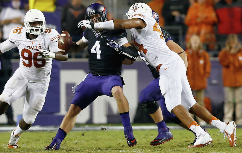FORT WORTH, TX - OCTOBER 26:  Casey Pachall #4 of the TCU Horned Frogs is sacked by Jackson Jeffcoat #44 of the Texas Longhorns as Chris Whaley #96 of the Texas Longhorns assists in the third quarter at Amon G. Carter Stadium on October 26, 2013 in Fort Worth, Texas. Photo: Tom Pennington, Getty Images / 2013 Getty Images
