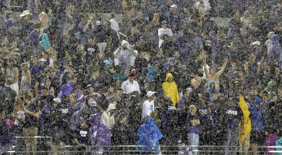 Fans sit in the stands in a heavy rain during a thunder delay in the second quarter of an NCAA college football game between Texas and TCU, Saturday, Oct. 26, 2013, in Fort Worth, Texas. (AP Photo/LM Otero) Photo: LM Otero, Associated Press / AP