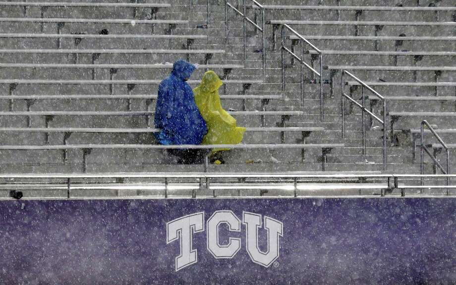 Fans sit in the stands during a thunder delay in the second quarter of an NCAA college football game between Texas and TCU, Saturday, Oct. 26, 2013, in Fort Worth, Texas. (AP Photo/LM Otero) Photo: LM Otero, Associated Press / AP