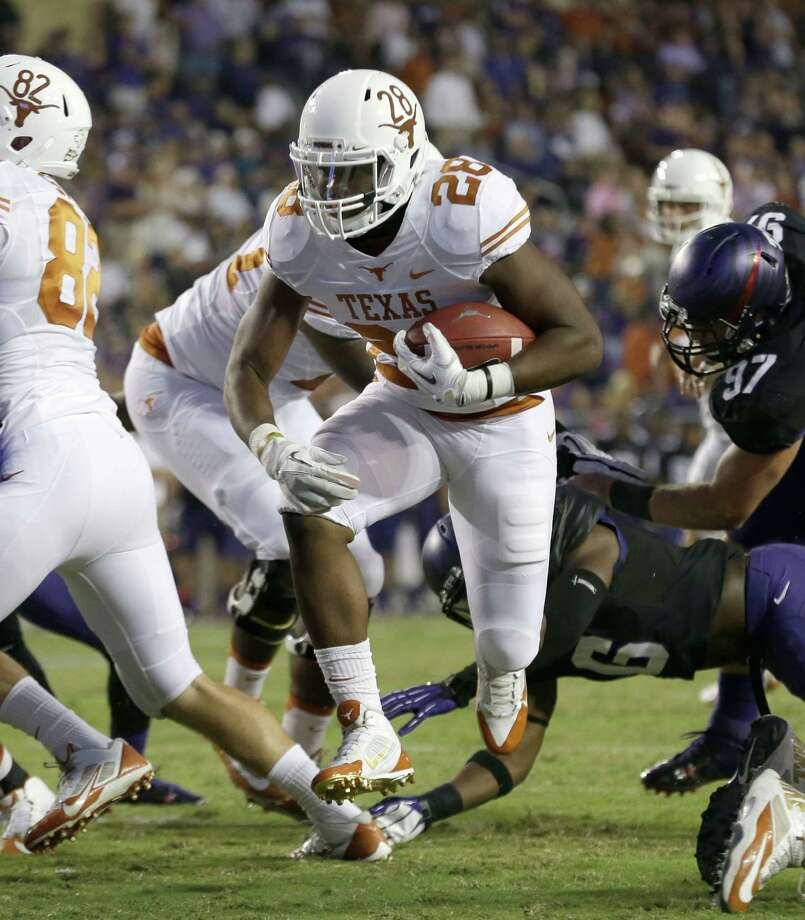Texas running back Malcolm Brown (28) finds a hole an runs in to scoring a touchdown during the first half of an NCAA college football game against TCU Saturday, Oct. 26, 2013, in Fort Worth, Texas. (AP Photo/LM Otero) Photo: LM Otero, Associated Press / AP
