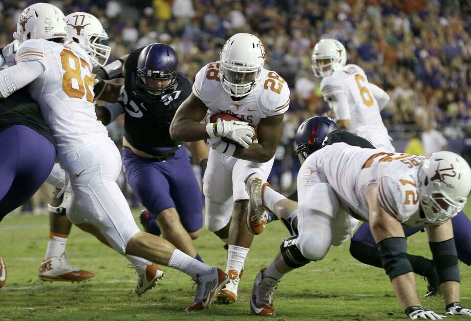 Texas running back Malcolm Brown (28) finds a hole and runs in to score a touchdown during the first half of an NCAA college football game against TCU, Saturday, Oct. 26, 2013, in Fort Worth, Texas.  Texas' Geoff Swaim (82) and Mason Walters (72) and TCU's Jon Koontz (97) are in on the play. (AP Photo/LM Otero) Photo: LM Otero, Associated Press / AP