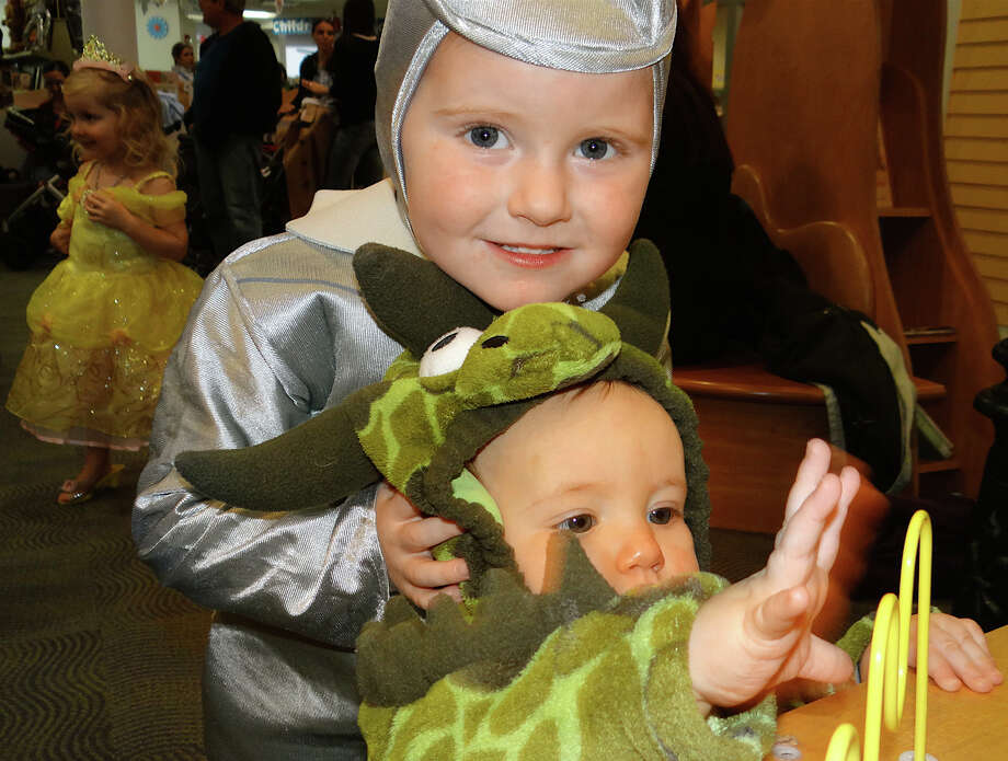 "Andrew Feeney, 3, of Fairfield, was the Tin Man from teh "" Wizard of Oz,"" with his sister Maeve, 9 months old, as a dinosaur at Fairfield Public Library's Halloween party Friday. Photo: Mike Lauterborn / Fairfield Citizen contributed"