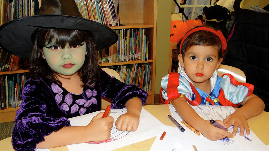 Gia Patrone, 4, of Fairfield, costumed as a witch, and her sister, Ellie, 2, as Snow White, at Friday's Halloween event at the Fairfield Public Library. Photo: Mike Lauterborn / Fairfield Citizen contributed