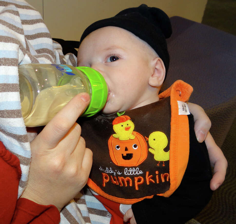 "Ten-week-old trick-or-treater Austin Dorsey, dressed as ""Daddy's Little Pumpkin,"" with mom at Fairfield Public Library's Halloween party on Friday. Photo: Mike Lauterborn / Fairfield Citizen contributed"