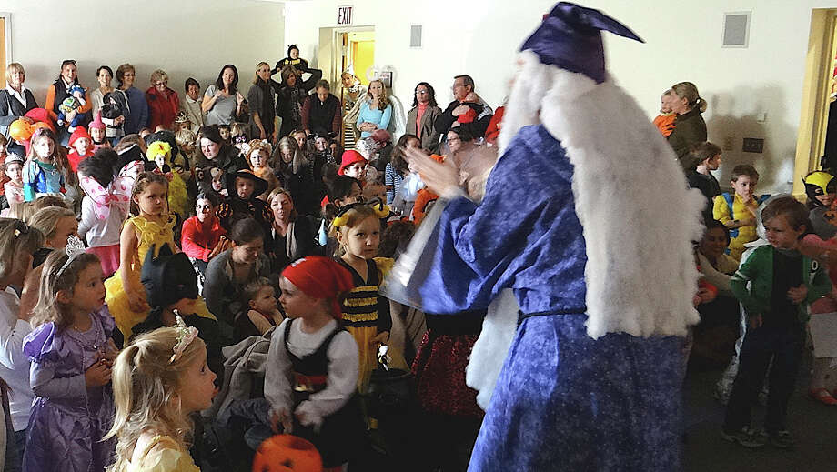 A wizard leads a sing-a-long with a costumed crowd of children at Friday's Halloween Extravaganza at the Fairfield Public Library. Photo: Mike Lauterborn / Fairfield Citizen contributed