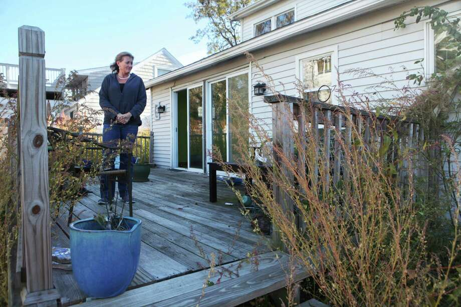 Charlotte Schmidt stands on the deck of her Milford Point home on Sunday, Oct. 27, 2013. Schmidt's home was damaged during Sandy last year and she is still unable to rebuild. Photo: BK Angeletti, B.K. Angeletti / Connecticut Post freelance B.K. Angeletti