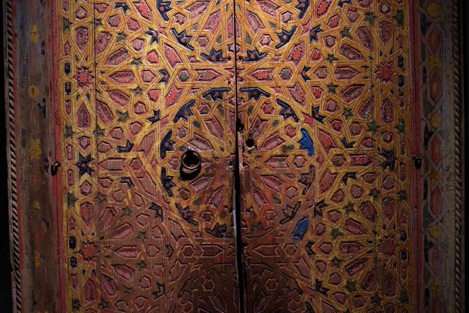 "A door from the Moroccan city of Fez, carved and painted with natural pigments and presumed to date from the 19th century, is displayed at the ""Nur: Light in art and science in the Islamic world"" exhibition in Seville, Spain, Friday, Oct 23, 2013. A private museum in the south of Spain is hosting an exhibition of rare Islamic art objects that highlight the role which enlightenment played in decoration and investigation in the Arab world. The exhibition, ""Nur: Light in art and science in the Islamic world,"" is sponsored by energy company Abengoa and has gathered together 150 pieces from collections like that of the Bodleian Library at Oxford University and private collectors across the world. From there, the entire exhibition travels to the Dallas Museum of Art in Texas. Photo: Laura Leon, AP / AP"