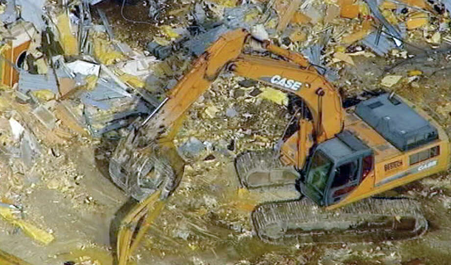In this image taken from video and provided by WABC-TV, a backhoe digs through the rubble as the demolition of Sandy Hook Elementary commences, Friday, Oct. 25, 2013 in Newtown, Conn. Neighbors of the elementary school where 20 children and six adults were shot dead in December 2012 expressed relief as workers tore down parts of it on Friday. (AP Photo/WABC-TV)  Photo: Uncredited, AP / ABC