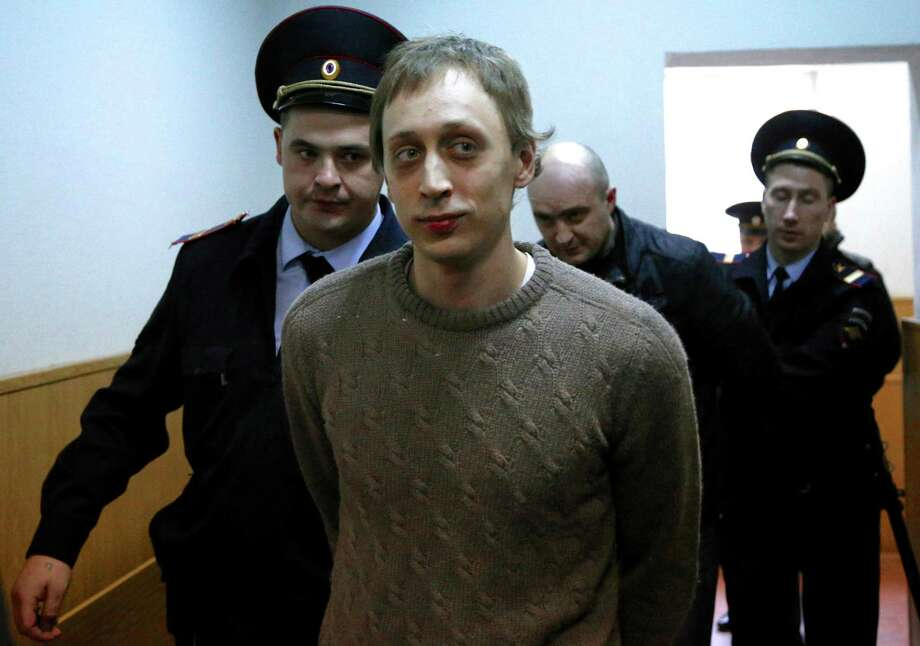 Pavel Dmitrichenko, center, is escorted to a court room in Moscow on Tuesday, Oct. 22, 2013. Bolshoi dancer Dmitrichenko goes on trial on  Tuesday, on charges of organizing an acid attack against the ballet's artistic director, Sergei Filin. Photo: Alexander Zemlianichenko, AP / AP2013