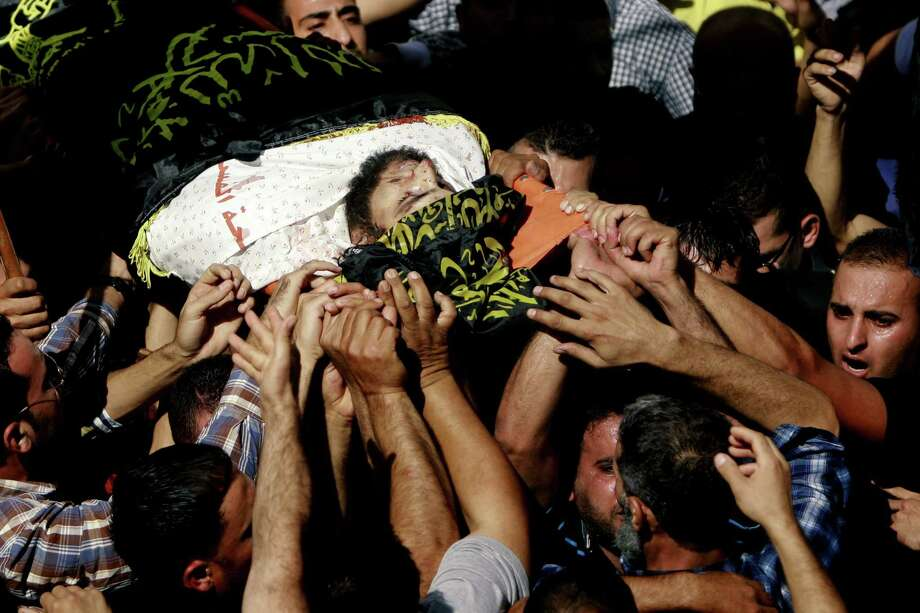 Palestinians carry the body of Islamic Jihad militant, Mohamed Aatzi wrapped in an Islamist flag during his funeral, in the village of Beit Laqiya near the West Bank city of Ramallah, Wednesday, Oct. 23, 2013. Israel's security service and the military say Israeli forces have killed Aatzi in the West Bank believed to be responsible for a Tel Aviv bus bombing last year. The green flags represent the ruling Hamas militant group. Photo: Majdi Mohammed, AP / AP2013