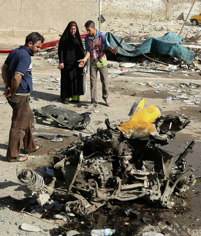 Citizens look at the site of a car bomb attack at a bus station in the Baghdad's eastern Mashtal neighborhood, Iraq, Sunday, Oct. 27, 2013. Insurgents on Sunday unleashed a new wave of car bombs in Shiite neighborhoods of Baghdad, killing and wounding dozens of people, officials said. Photo: Khalid Mohammed, AP / AP2013