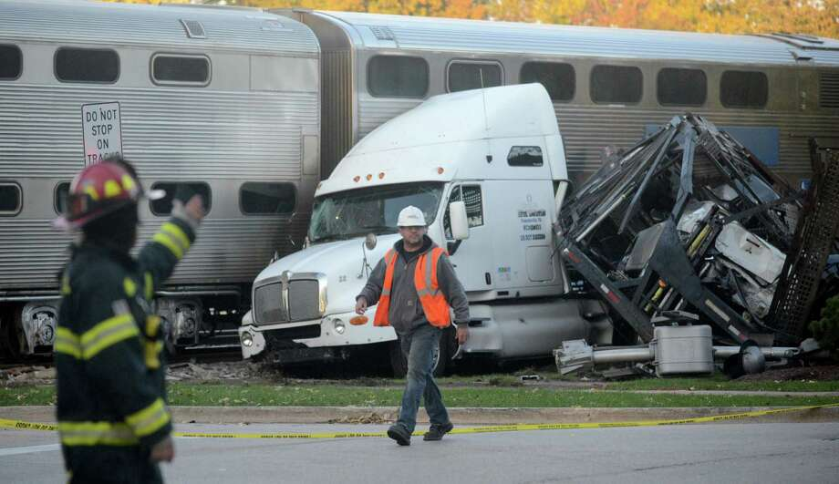 Metra officials say a commuter train has hit a semitrailer carrying cars near the Chicago suburb of Bartlett, which caused a minor derailment Monday Oct. 21, 2013. Metra spokeswoman Meg Reile says a train from Elgin toward the city hit the semi around 3:30 p.m. Monday as it was arriving at the Bartlett depot. The crash shut down service on the Milwaukee District West Line. It also damaged and derailed the front car of the train. Photo: Patrick Kunzer, AP / Daily Herald