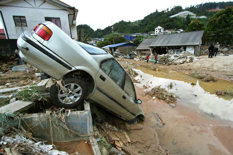 People stand near a car destroyed by a mud slide in Cameron Highlands, Malaysia, Wednesday, Oct. 23, 2013. Several people were killed after water released from a dam sparked a flash flood in the Malaysian resort area, according to local sources. Photo: Peter Liow, AP / AP2013