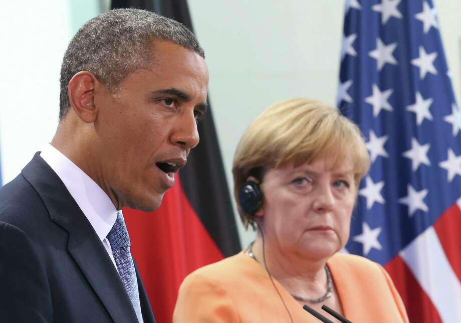"In this June 19, 2013 file picture US President Barack Obama speaks  during a  press conference with German Chancellor Angela Merkel, right, at the  Chancellery in Berlin. Germany's interior minister is pressing for ""complete information"" from Washington on the alleged U.S. surveillance of Chancellor Angela Merkel's  cellphone. Merkel complained to President Barack Obama on Wednesday after receiving information her phone may have been monitored.  Interior Minister Hans-Peter Friedrich was quoted Sunday Oct. 27, 2013  as telling newspaper Bild am Sonntag he wants ""complete information on all accusations"" and that ""if the Americans intercepted cellphones in Germany, they broke German law on German soil."" He added wiretapping is a crime and ""those responsible must be held accountable."" Photo: Michael Kappeler, AP / AP2013"