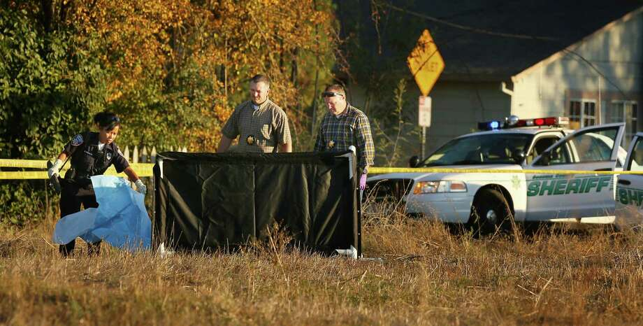 In this photo taken Tuesday Oct. 22, 2013, law enforcement investigators cover the body of a 13-year-old boy shot and killed by officers in Santa Rosa, Calif.  Two California sheriff's deputies saw the boy walking with what appeared to be a high-powered weapon Tuesday, sheriff's Lt. Dennis O'Leary said. The replica gun resembled an AK-47, according to a photograph released by the sheriff's office. Deputies learned after the shooting that it wasn't an actual firearm, according to O'Leary. The teen was pronounced dead at the scene. The deputies, who have not been identified, have been placed on administrative leave, which is standard after a shooting, O'Leary said. Photo: Conner Jay, AP / AP2013