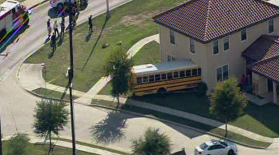This photo from video provided by KENS 5 San Antonio, shows a school bus that crashed into a house at Joint Base San Antonio-Fort Sam Houston, Texas, on Friday, Oct. 25, 2013. Three children and two adults have suffered minor injuries. (AP Photo/KENS 5 San Antonio) Photo: Uncredited, AP / AP2013