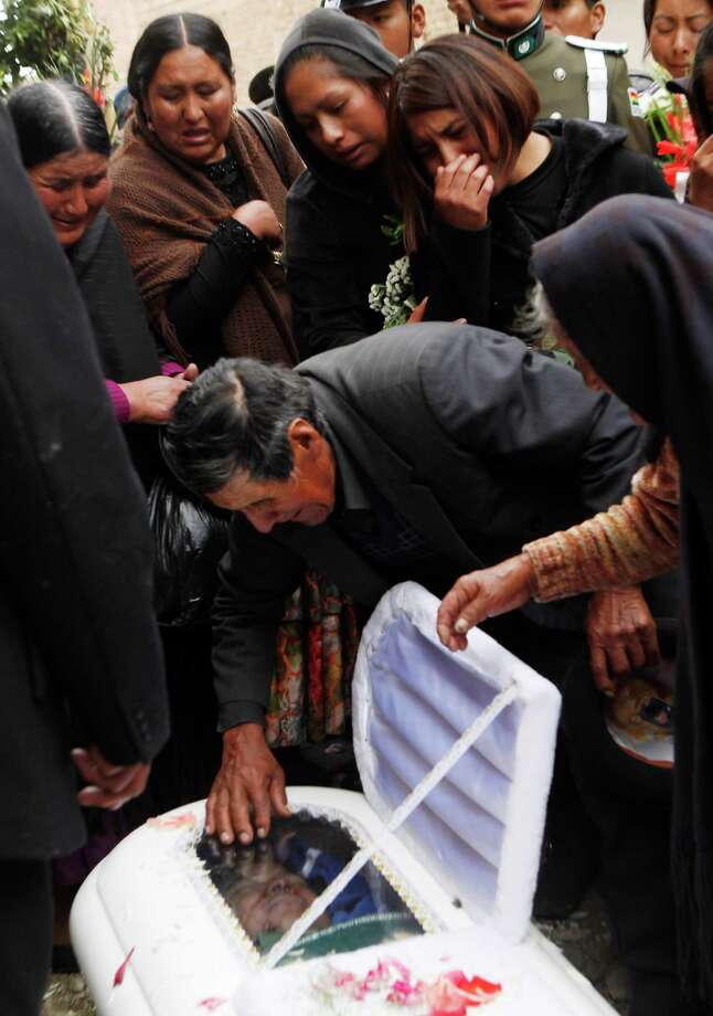 Relatives of Jhonny Quispe Chura mourn over his body during a funeral at the cemetery in La Paz, Bolivia, Monday, Oct. 21, 2013. A group of locals attacked police and soldiers who were destroying illegal coca crops in the municipality of Apolo, about 90 miles (55 kilometers) north of La Paz on Oct. 19, killing at least a soldier and a police officer, authorities said. Photo: Juan Karita, AP / AP