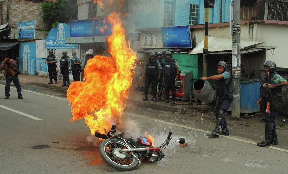 Bangladeshi police officers try to douse the flames on a motorcycle allegedly ignited  by opposition activists during a general strike in Rajshahi, outskirts of Dhaka, Bangladesh, Sunday, Oct. 27, 2013.  Police and supporters of Bangladesh's ruling party clashed Sunday with opposition supporters, leaving fatalities and scores injured in different parts of the country as opposition parties tried to enforce a three-day nationwide general strike. Photo: Uncredited, AP / AP2013