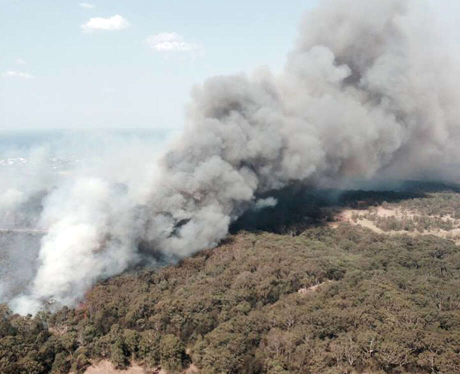 In this photo provided by the New South Wales Rural Fire Service, smoke rises from a wildfire near Lake Macquarie, New South Wales, Australia, Wednesday, Oct. 23, 2013.  Winds that were fanning wildfires and showering embers on threatened communities eased late Wednesday, after scores of Australians evacuated their homes in mountains west of Sydney. Photo: Uncredited, AP / AP2013