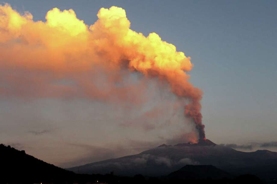 Smoke billows during an eruption of Mount Etna volcano as seen from the village of Viagrande, near the Sicilian town of Catania, Italy, Saturday, Oct. 26, 2013. Mount Etna, Europe's most active volcano, has erupted, sending up a towering plume of ash visible in much of eastern Sicily. Etna's eruptions are not infrequent, although the last major one occurred in 1992. Catania airport said the eruption Saturday forced closure of nearby air space before dawn, but authorities lifted the closure in early morning. Several inhabited villages dot the mountain's slopes, but evacuations weren't necessary despite the lava flow. Photo: Carmelo Imbesi, AP / THE ASSOCIATED PRESS2013