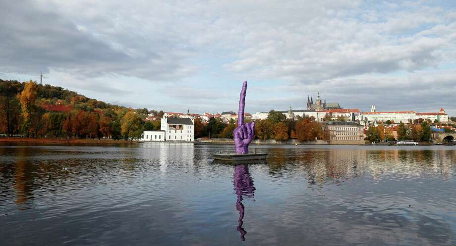 A statue by Czech sculptor David Cerny is placed on the Vltava river in Prague, Czech Republic, Monday, Oct. 21, 2013. A Czech artist known for his anti-communist stance has floated a huge statue of a hand making an obscene gesture on Prague's main river, days before parliamentary elections that could give the communists a taste of power almost a quarter-century after they were ousted.The Associated Press reports: A special parliamentary election held in the Czech Republic left no party with a majority on Saturday, which could lead to protracted negotiations aimed at forming a coalition government. Photo: Petr David Josek, AP / AP2013