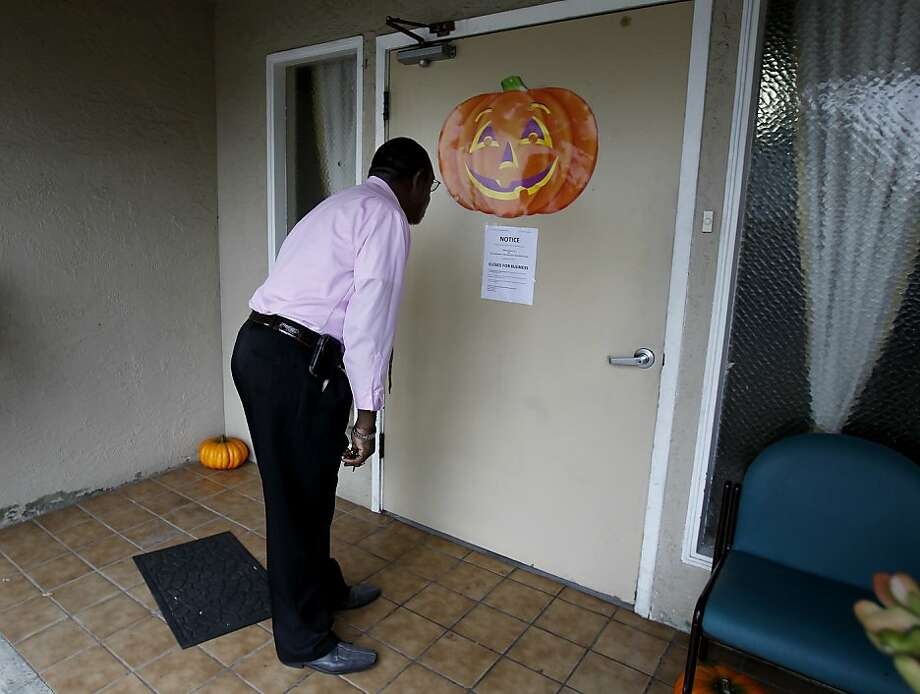 Deacon Oscar Moore Jr., who came to visit a relative, reads the notice on the front door of Valley Manor Residential Care in Castro Valley, which was shut down by the state. Photo: Brant Ward, The Chronicle